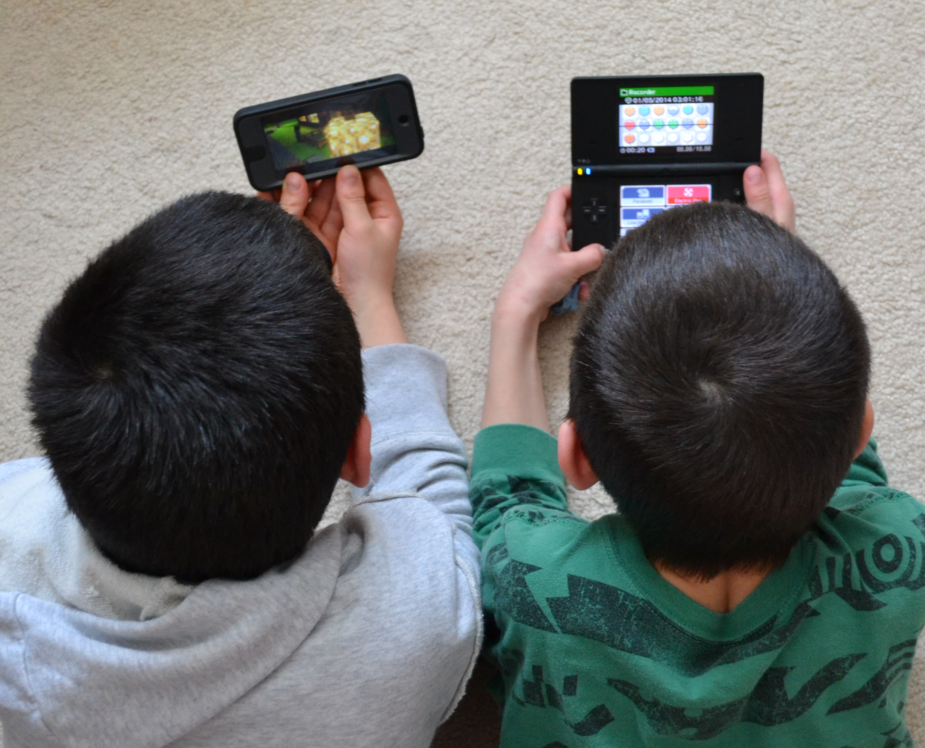 two boys holding handheld devices